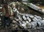 a man sits beside trash of his home demolished