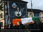 mourners walk with pall bearers as they carry3