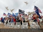 demonstrators send off white doves from the beach