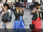 women use their mobile phones in duomo square