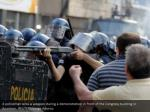 a policeman aims a weapon during a demonstration