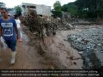people walk in a destroyed area after heavy rains