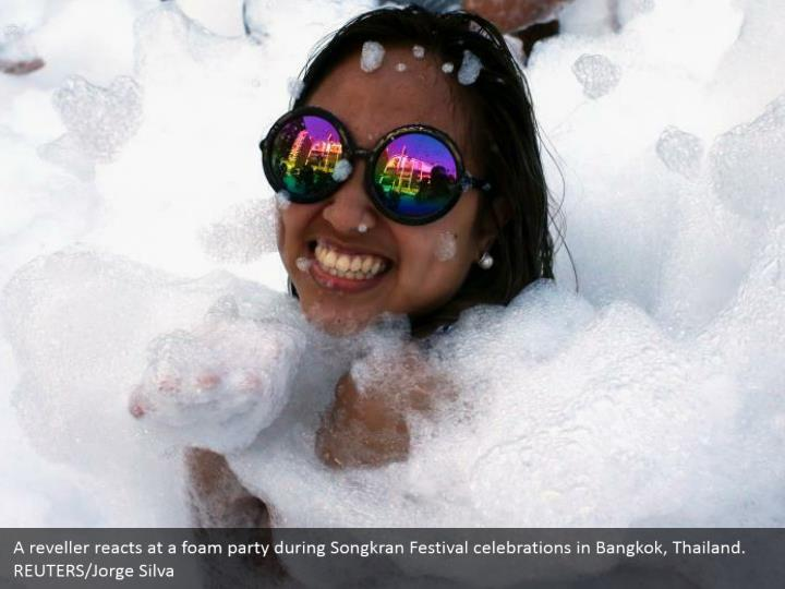 A reveller reacts at a foam party during Songkran Festival celebrations in Bangkok, Thailand. REUTERS/Jorge Silva