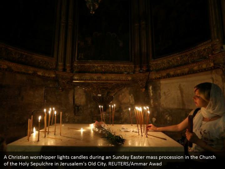 A Christian worshipper lights candles during an Sunday Easter mass procession in the Church of the Holy Sepulchre in Jerusalem's Old City. REUTERS/Ammar Awad