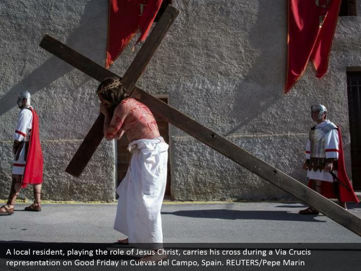 A local resident, playing the role of Jesus Christ, carries his cross during a Via Crucis representation on Good Friday in Cuevas del Campo, Spain. REUTERS/Pepe Marin