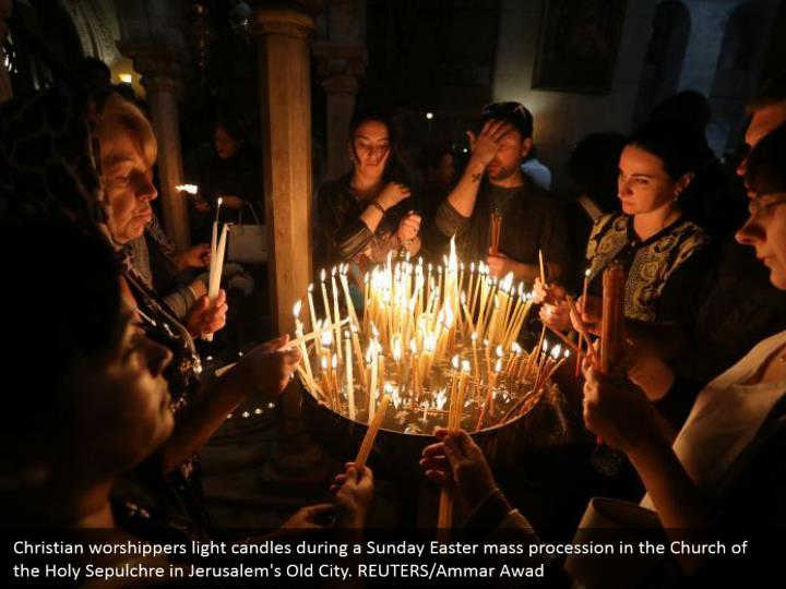 Christian worshippers light candles during a Sunday Easter mass procession in the Church of the Holy Sepulchre in Jerusalem's Old City. REUTERS/Ammar Awad