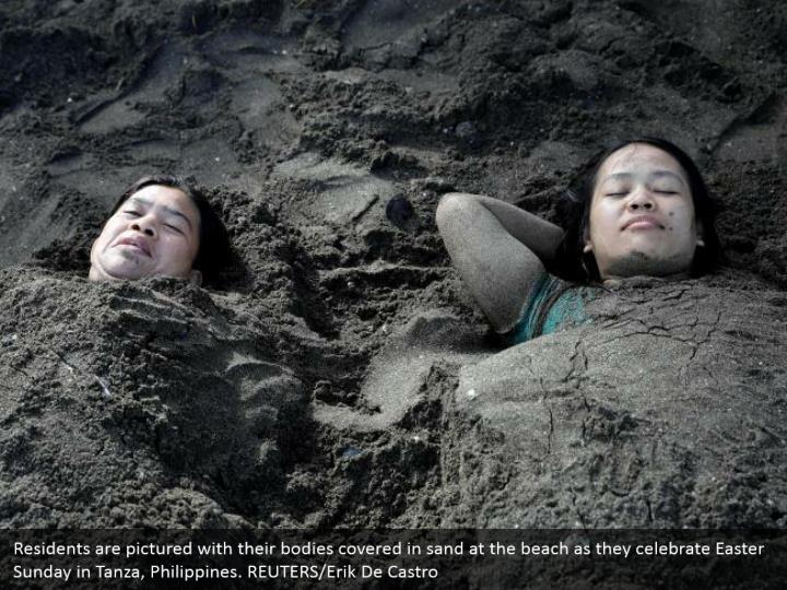 Residents are pictured with their bodies covered in sand at the beach as they celebrate Easter Sunday in Tanza, Philippines. REUTERS/Erik De Castro