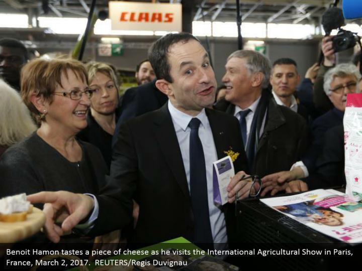 Benoit Hamon tastes a piece of cheese as he visits the International Agricultural Show in Paris, France, March 2, 2017.  REUTERS/Regis Duvignau