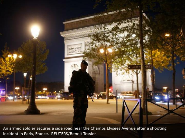 An armed soldier secures a side road near the Champs Elysees Avenue after a shooting incident in Paris, France.  REUTERS/Benoit Tessier