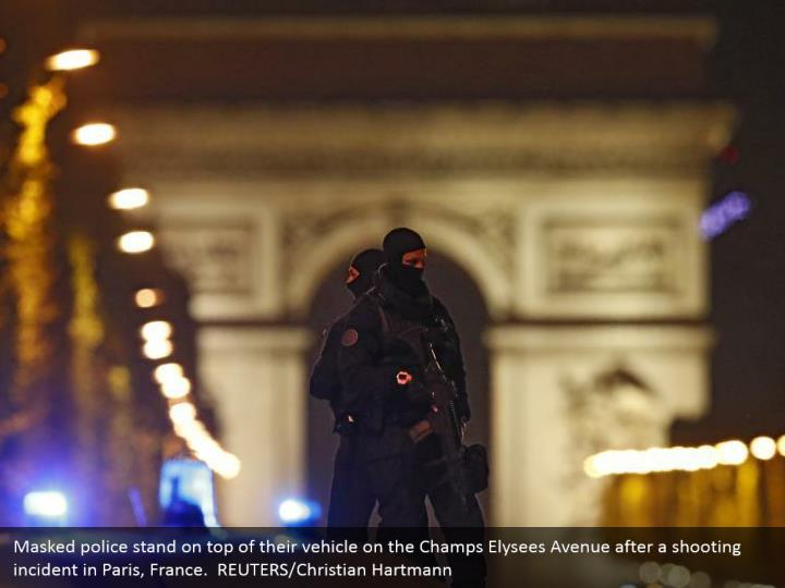 Masked police stand on top of their vehicle on the Champs Elysees Avenue after a shooting incident in Paris, France.  REUTERS/Christian Hartmann