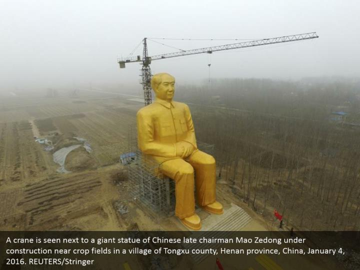 A crane is seen next to a giant statue of Chinese late chairman Mao Zedong under construction near crop fields in a village of Tongxu county, Henan province, China, January 4, 2016. REUTERS/Stringer