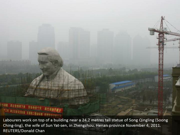 Labourers work on top of a building near a 24.2 metres tall statue of Song Qingling (Soong Ching-ling), the wife of Sun Yat-sen, in Zhengzhou, Henan province November 4, 2011. REUTERS/Donald Chan