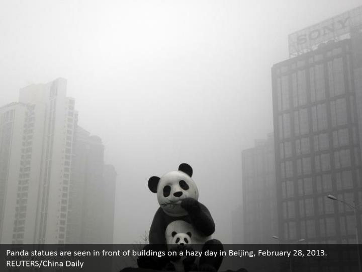 Panda statues are seen in front of buildings on a hazy day in Beijing, February 28, 2013. REUTERS/China Daily