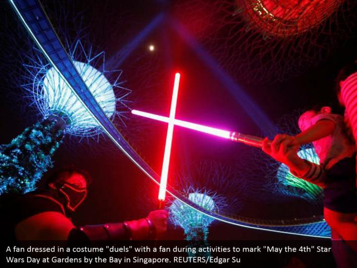 """A fan dressed in a costume """"duels"""" with a fan during activities to mark """"May the 4th"""" Star Wars Day at Gardens by the Bay in Singapore. REUTERS/Edgar Su"""
