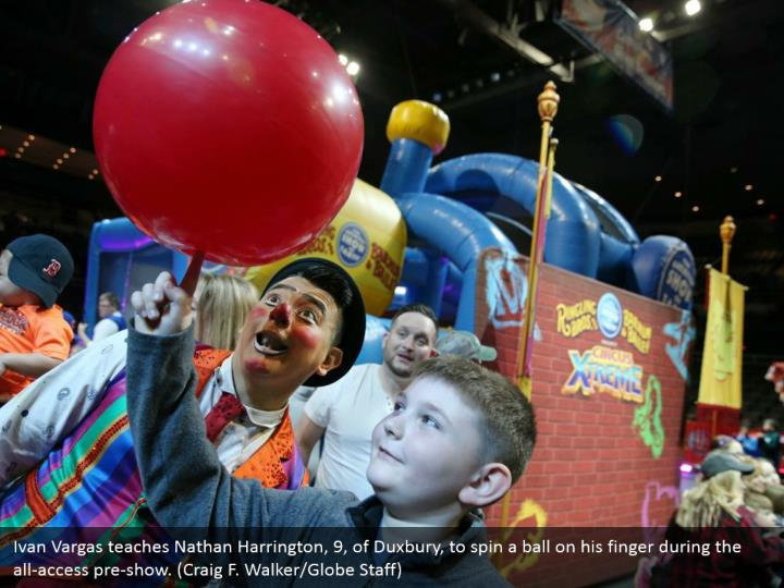 Ivan Vargas teaches Nathan Harrington, 9, of Duxbury, to spin a ball on his finger during the all-access pre-show. (Craig F. Walker/Globe Staff)