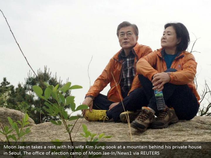 Moon Jae-in takes a rest with his wife Kim Jung-sook at a mountain behind his private house in Seoul. The office of election camp of Moon Jae-In/News1 via REUTERS