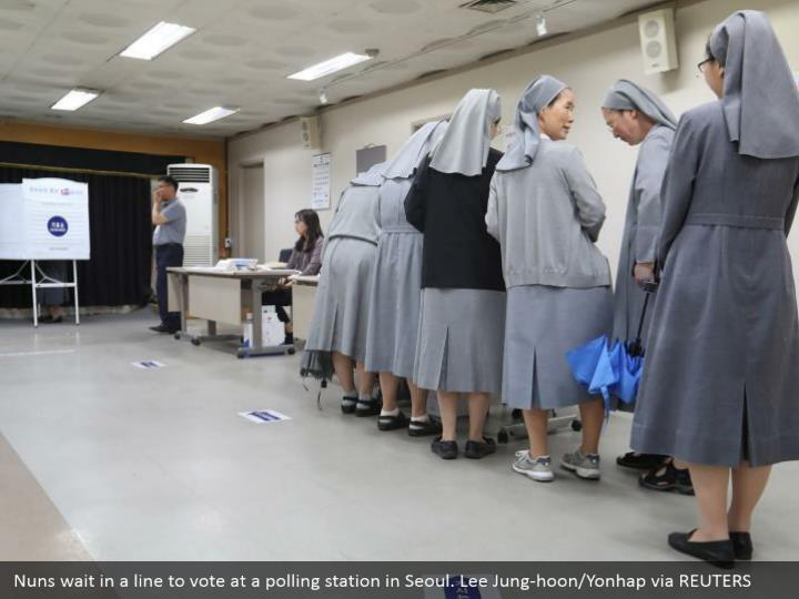 Nuns wait in a line to vote at a polling station in Seoul. Lee Jung-hoon/Yonhap via REUTERS
