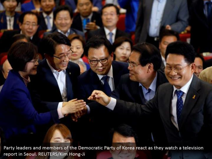 Party leaders and members of the Democratic Party of Korea react as they watch a television report in Seoul. REUTERS/Kim Hong-Ji