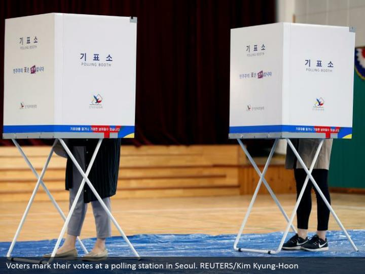 Voters mark their votes at a polling station in Seoul. REUTERS/Kim Kyung-Hoon