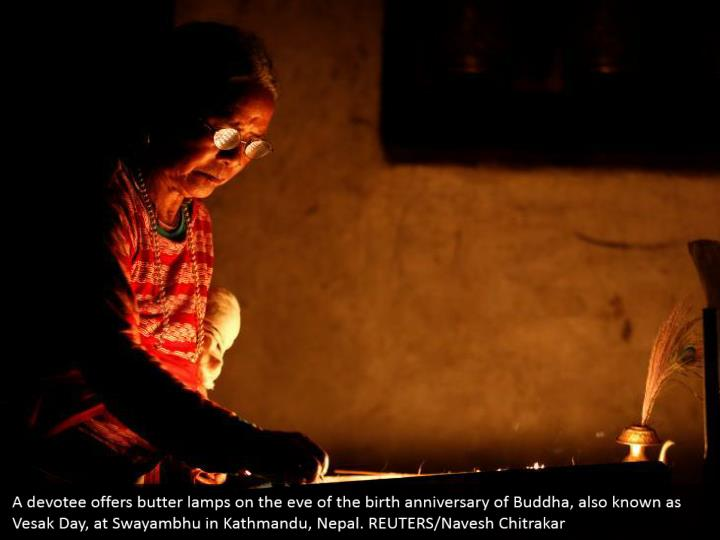 A devotee offers butter lamps on the eve of the birth anniversary of Buddha, also known as Vesak Day, at Swayambhu in Kathmandu, Nepal. REUTERS/Navesh Chitrakar