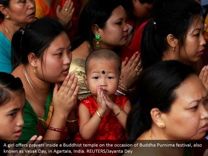 A girl offers prayers inside a Buddhist temple on the occasion of Buddha Purnima festival, also known as Vesak Day, in Agartala, India. REUTERS/Jayanta Dey