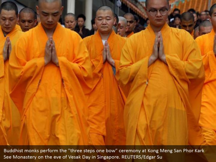 """Buddhist monks perform the """"three steps one bow"""" ceremony at Kong Meng San Phor Kark See Monastery on the eve of Vesak Day in Singapore. REUTERS/Edgar Su"""