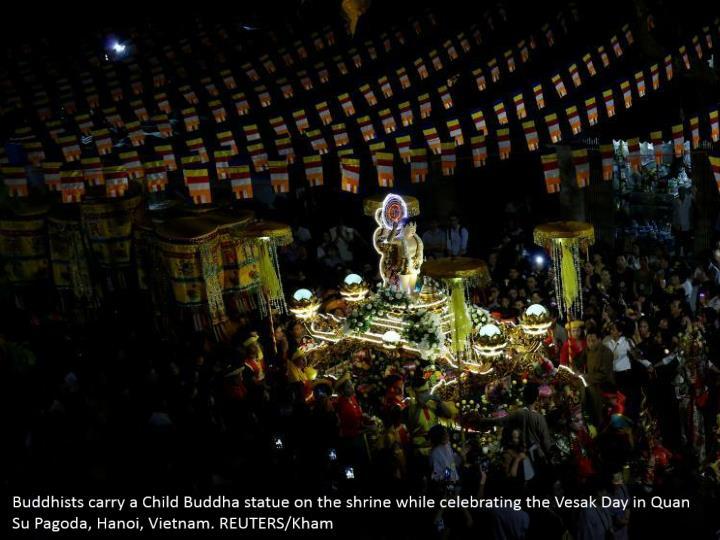 Buddhists carry a Child Buddha statue on the shrine while celebrating the Vesak Day in Quan Su Pagoda, Hanoi, Vietnam. REUTERS/Kham