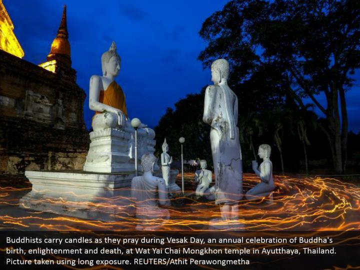 Buddhists carry candles as they pray during Vesak Day, an annual celebration of Buddha's birth, enlightenment and death, at Wat Yai Chai Mongkhon temple in Ayutthaya, Thailand. Picture taken using long exposure. REUTERS/Athit Perawongmetha