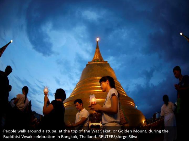 People walk around a stupa, at the top of the Wat Saket, or Golden Mount, during the Buddhist Vesak celebration in Bangkok, Thailand. REUTERS/Jorge Silva