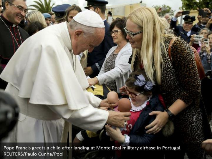 Pope Francis greets a child after landing at Monte Real military airbase in Portugal. REUTERS/Paulo Cunha/Pool