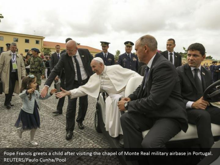 Pope Francis greets a child after visiting the chapel of Monte Real military airbase in Portugal.  REUTERS/Paulo Cunha/Pool