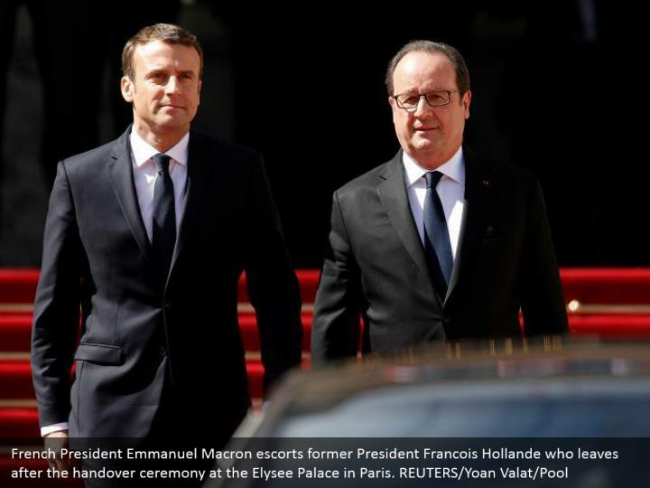 French President Emmanuel Macron escorts former President Francois Hollande who leaves after the handover ceremony at the Elysee Palace in Paris. REUTERS/Yoan Valat/Pool