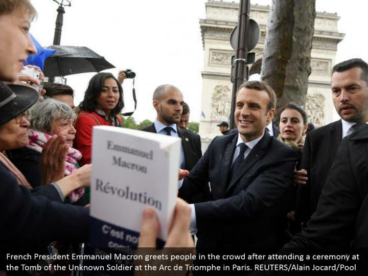 French President Emmanuel Macron greets people in the crowd after attending a ceremony at the Tomb of the Unknown Soldier at the Arc de Triomphe in Paris. REUTERS/Alain Jocard/Pool