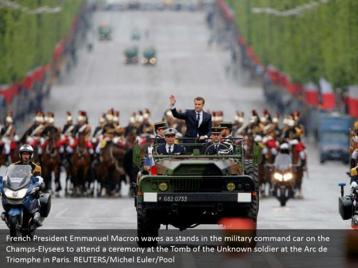 French President Emmanuel Macron waves as stands in the military command car on the Champs-Elysees to attend a ceremony at the Tomb of the Unknown soldier at the Arc de Triomphe in Paris. REUTERS/Michel Euler/Pool