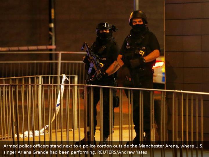Armed police officers stand next to a police cordon outside the Manchester Arena, where U.S. singer Ariana Grande had been performing. REUTERS/Andrew Yates