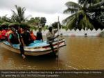 people travel in a boat on a flooded road during