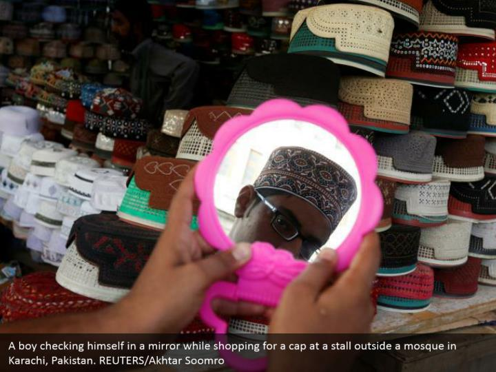 A boy checking himself in a mirror while shopping for a cap at a stall outside a mosque in Karachi, Pakistan. REUTERS/Akhtar Soomro