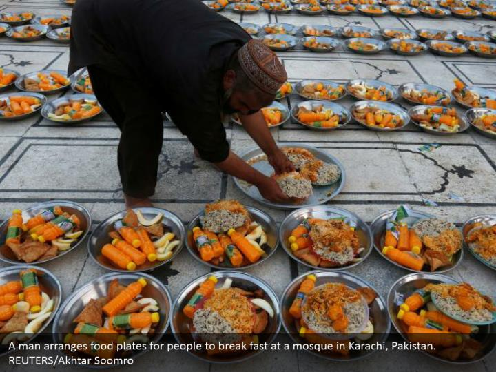 A man arranges food plates for people to break fast at a mosque in Karachi, Pakistan. REUTERS/Akhtar Soomro