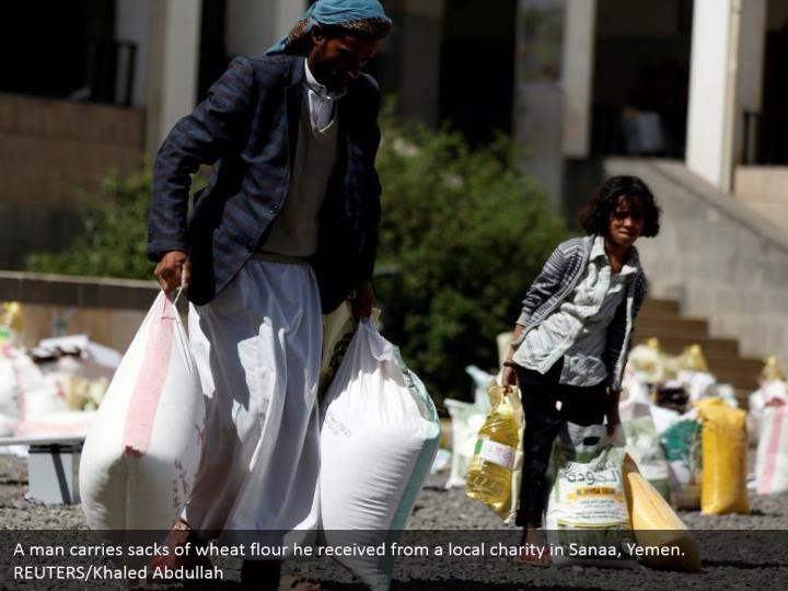 A man carries sacks of wheat flour he received from a local charity in Sanaa, Yemen. REUTERS/Khaled Abdullah