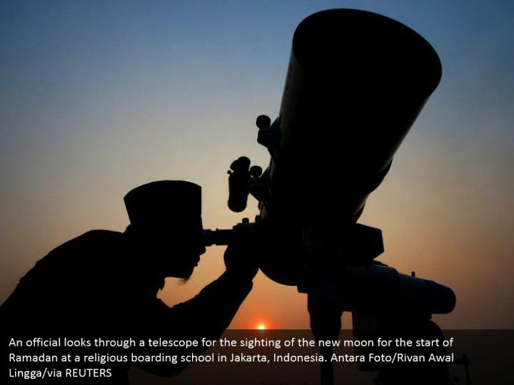 An official looks through a telescope for the sighting of the new moon for the start of Ramadan at a religious boarding school in Jakarta, Indonesia. Antara Foto/Rivan Awal Lingga/via REUTERS