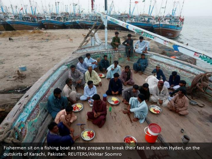 Fishermen sit on a fishing boat as they prepare to break their fast in Ibrahim Hyderi, on the outskirts of Karachi, Pakistan. REUTERS/Akhtar Soomro