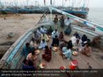 fishermen sit on a fishing boat as they prepare