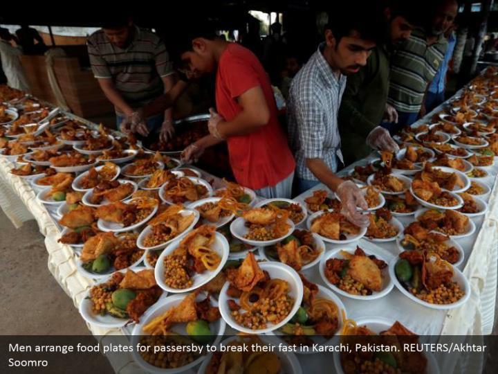 Men arrange food plates for passersby to break their fast in Karachi, Pakistan. REUTERS/Akhtar Soomro