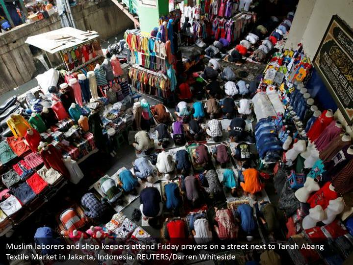 Muslim laborers and shop keepers attend Friday prayers on a street next to Tanah Abang Textile Market in Jakarta, Indonesia. REUTERS/Darren Whiteside