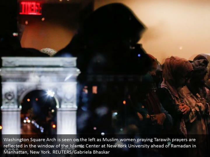 Washington Square Arch is seen on the left as Muslim women praying Tarawih prayers are reflected in the window of the Islamic Center at New York University ahead of Ramadan in Manhattan, New York. REUTERS/Gabriela Bhaskar