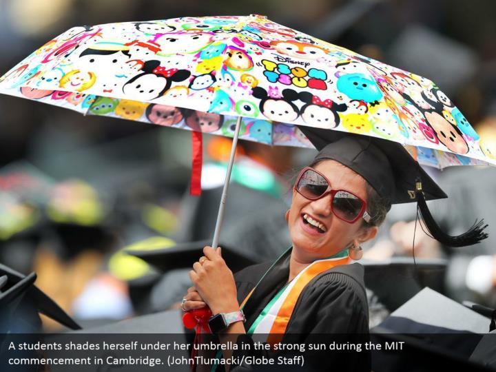 A students shades herself under her umbrella in the strong sun during the MIT commencement in Cambridge. (JohnTlumacki/Globe Staff)