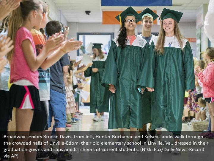 Broadway seniors Brooke Davis, from left, Hunter Buchanan and Kelsey Landis walk through the crowded halls of Linville-Edom, their old elementary school in Linville, Va., dressed in their graduation gowns and caps amidst cheers of current students. (Nikki Fox/Daily News-Record via AP)