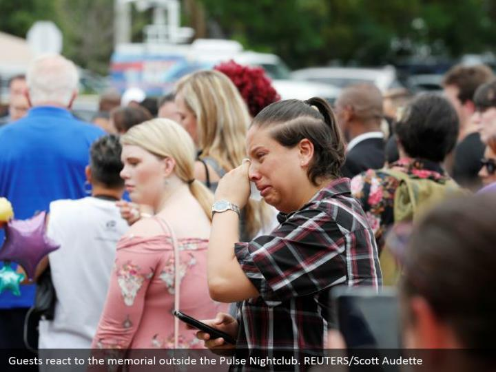 Guests react to the memorial outside the Pulse Nightclub. REUTERS/Scott Audette