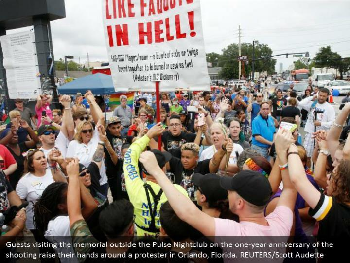 Guests visiting the memorial outside the Pulse Nightclub on the one-year anniversary of the shooting raise their hands around a protester in Orlando, Florida. REUTERS/Scott Audette