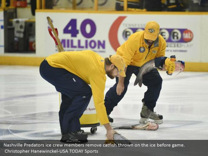 Nashville Predators ice crew members remove catfish thrown on the ice before game.  Christopher Hanewinckel-USA TODAY Sports